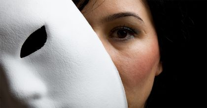 Woman peeking from behind white drama mask